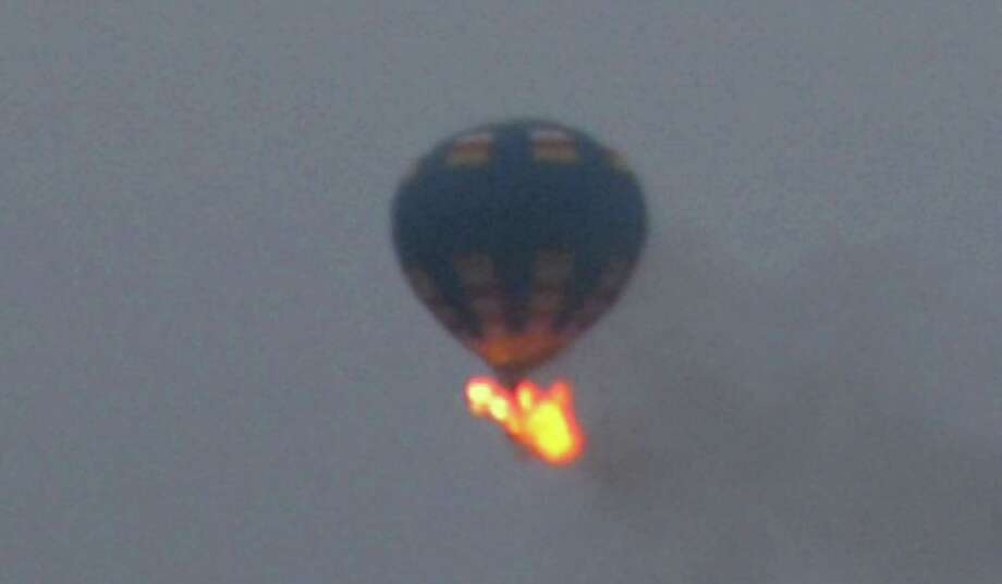 The balloon that crashed hit a power line and caught fire. Witnesses reported hearing the noise of an explosion aboard the craft. Photo: Nancy Johnson / Associated Press / AP