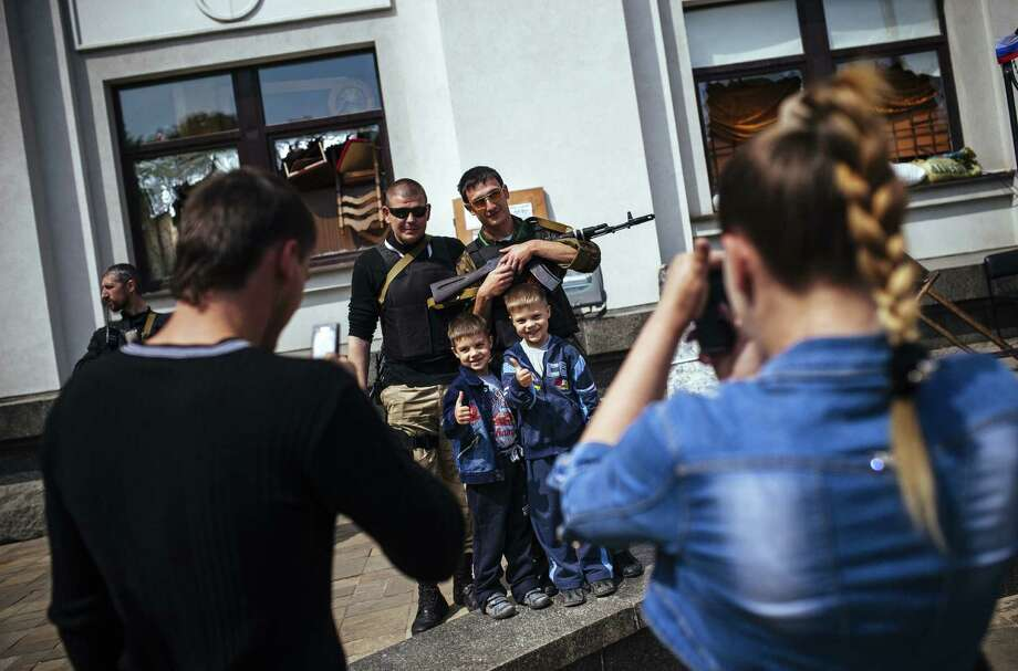 A family takes pictures of their children posing with pro-Russian activists in the eastern Ukrainian city of Luhansk on the eve of a referendum on independence in the Luhansk and Donetsk regions. Photo: Dimitar Dilkoff / Getty Images / AFP