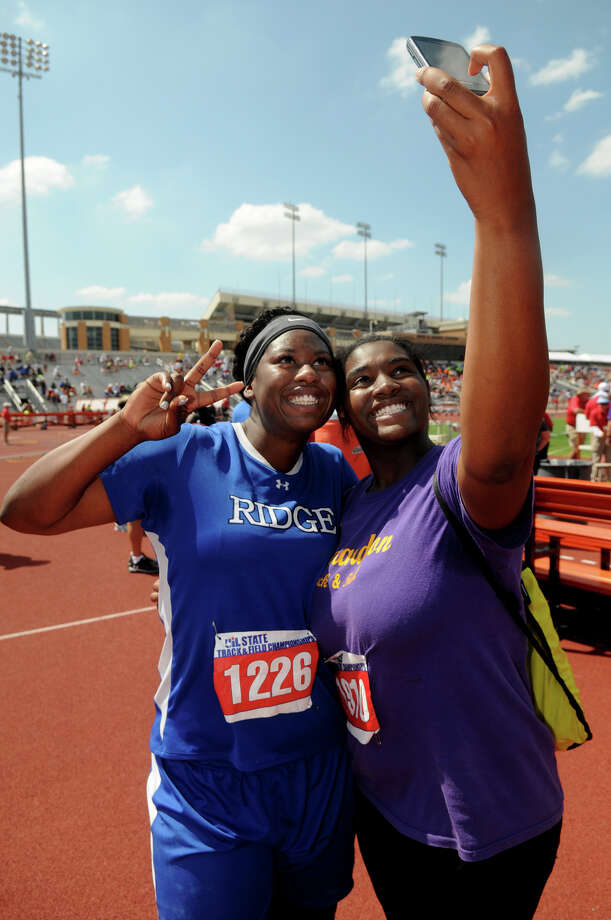 Oak Ridge senior N'Dia Warren-Jaques, left, shares a photo with fellow shot-putter Asia Abron, a sophomore from Richardson High School, after Warren-Jaques won the Class 5A Girls Shot Put during the UIL State Track & Field Championships at Mike A. Meyers Stadium in Austin on Saturday. Photo: Jerry Baker, For The Chronicle