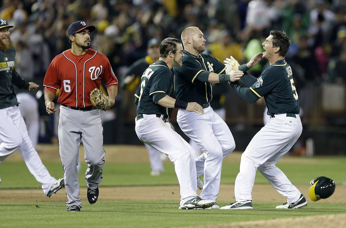 Oakland Athletics' John Jaso, right, celebrates after making the game-winning hit against the Washington Nationals in the 10th inning of a baseball game Saturday, May 10, 2014, in Oakland, Calif. At left is Nationals' Anthony Rendon (6). (AP Photo/Ben Margot)