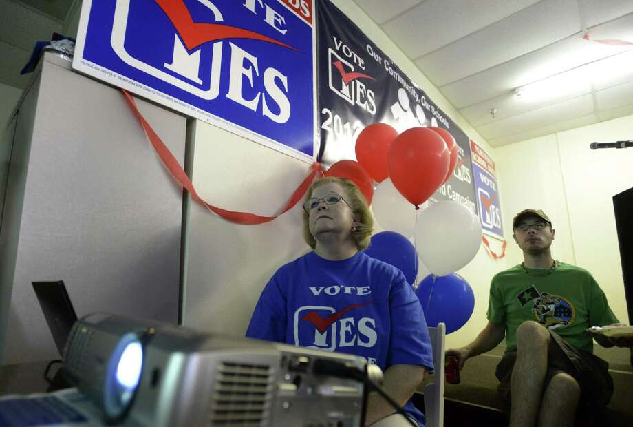 Monica Faulkenbery runs the projector and watches returns at Northside Bond campaign headquarters  Saturday. Voters approved a $648.3 million bond package to build 409 classrooms and renovate many Northside Schools. Photo: Billy Calzada / San Antonio Express-News / San Antonio Express-News