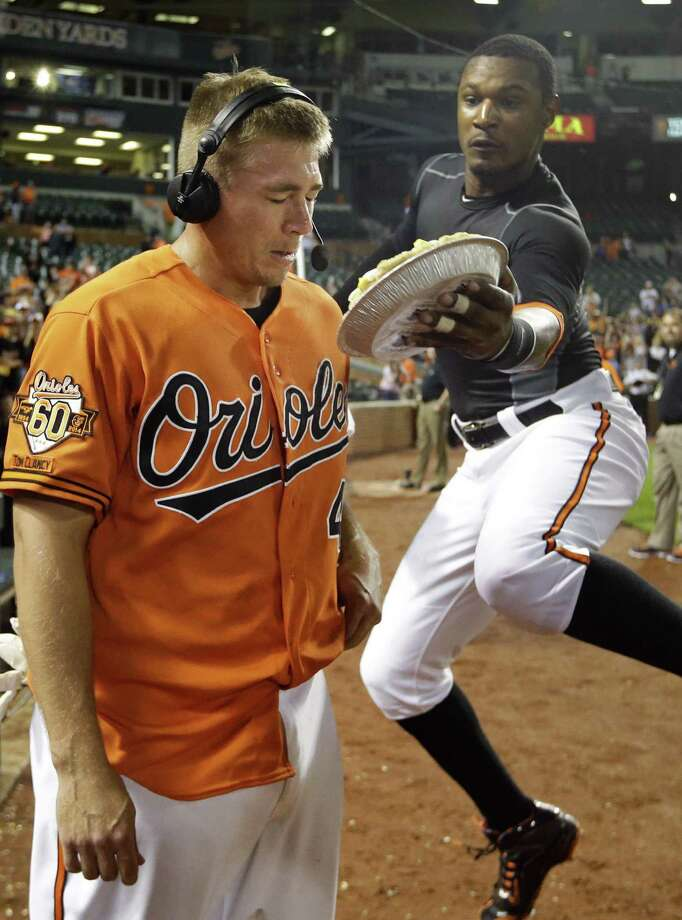 Baltimore's Steve Clevenger, whose RBI double in the 10th won the game, gets a celebratory pie to the face from Adam Jones as he does an interview. Photo: Patrick Semansky / Associated Press / AP