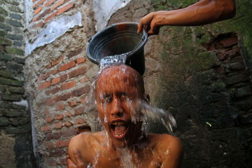 Tasikmalaya Indonesia  City new picture : TASIKMALAYA, INDONESIA MAY 10: An officer throws water onto a mental ...