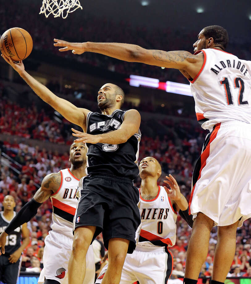 San Antonio Spurs' Tony Parker shoots between Portland Trail Blazers' Thomas Robinson (from left), Damian Lillard, and LaMarcus Aldridge during first half action of Game 3 in the Western Conference semifinals Saturday May 10, 2014 at the Moda Center in Portland, OR. Photo: San Antonio Express-News / © 2014 San Antonio Express-News