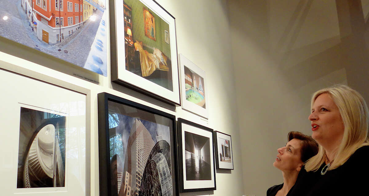 Fairfielders Annette Alfieri and Connie Cusick admire photographs at Fairfield Museum and History Center's Images 2014 opening reception Saturday night.