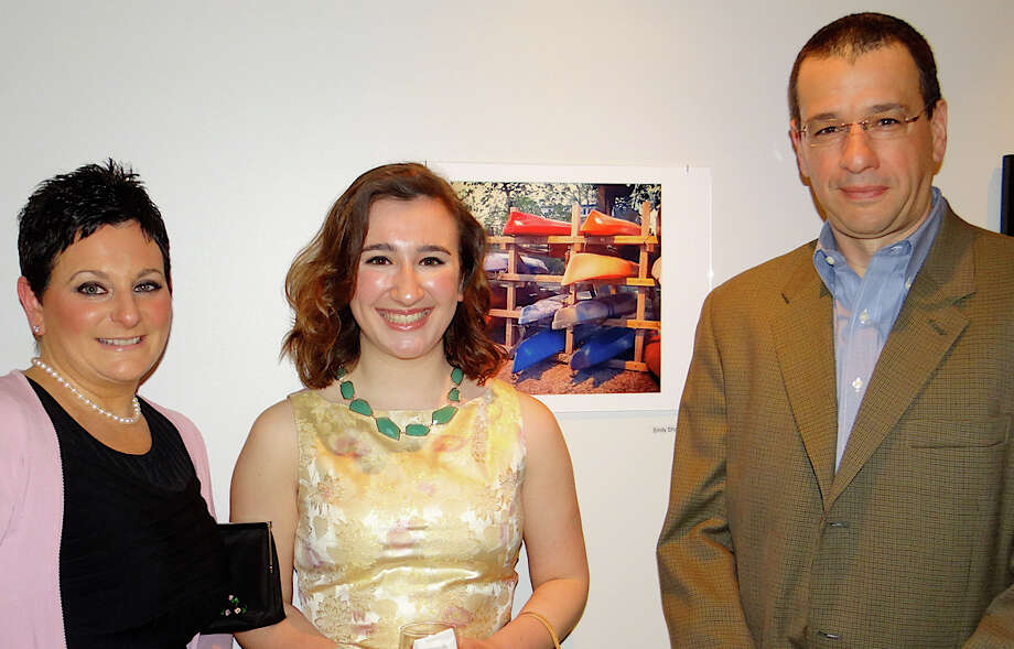 "Danielle and Bill Sharp of Fairfield with their daughter Emily and her photo, titled ""Beached,"" at Fairfield Museum and History Center's Images 2014 exhibit. Photo: Mike Lauterborn / Fairfield Citizen"