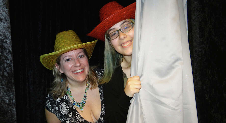 Heather Hamilton and Sacha Ruiz-Macheret peek out of a photo booth at Fairfield Museum and History Center's Images 2014 opening reception Saturday. Photo: Mike Lauterborn / Fairfield Citizen