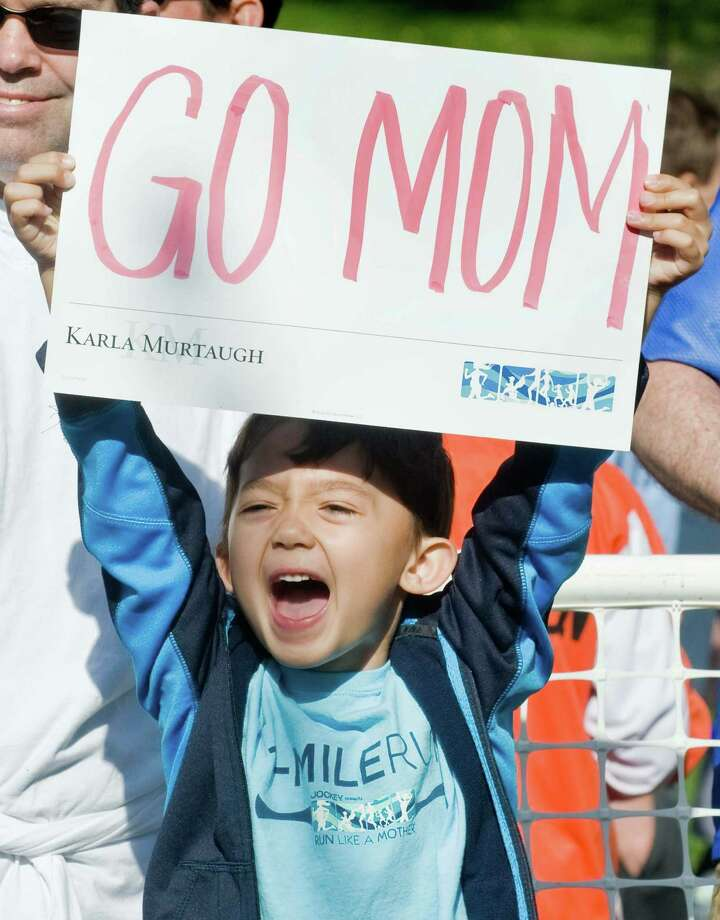 "Seven-year-old J.W. Mooney of Ridgefield cheers his mother on during the ""Run Like a Mother"" 5K annual Mother's Day race in Ridgefield. Sunday, May 11, 2014 Photo: Scott Mullin / The News-Times Freelance"