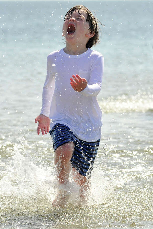 Dane Fishback runs through the water at Greenwich Point Park beach in Greenwich, Conn., on Sunday, May 11, 2014. Photo: Jason Rearick / Stamford Advocate
