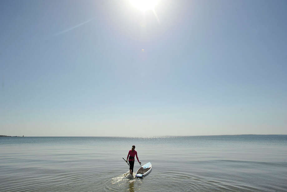 Suzanne Timerman takes her paddleboard out on the calm waters of Long Island Sound at Greenwich Point Park beach in Greenwich, Conn., on Sunday, May 11, 2014. Photo: Jason Rearick / Stamford Advocate