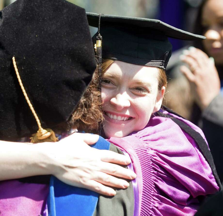 Amy Nassef receives a hug during the graduation ceremony at Western Connecticut State University. Sunday, May 11, 2014 Photo: Scott Mullin / The News-Times Freelance