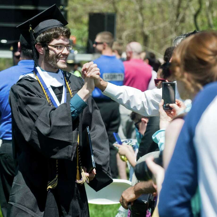 David Arana is congratulated from a member of the crowd after receiving his diploma at the graduation ceremony at Western Connecticut State University. Sunday, May 11, 2014 Photo: Scott Mullin / The News-Times Freelance