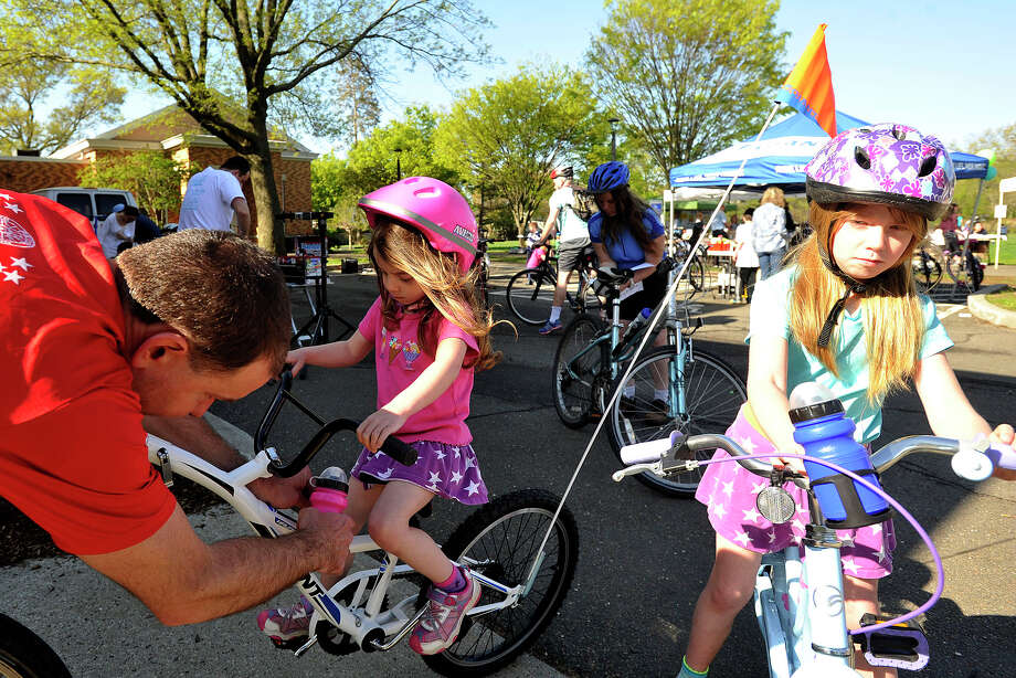 Rachelle Matchen looks on as her father, Paul Matchen, adjusts her water bottle as Alycia Matchen, center background, and Jacqui Matchen, right, wait to start the 12th annual Old Greenwich - Riverside Community Center's Mother's Day Bike Ride at Old Greenwich Elementary School in Greenwich, Conn., on Sunday, May 11, 2014. Photo: Jason Rearick / Stamford Advocate