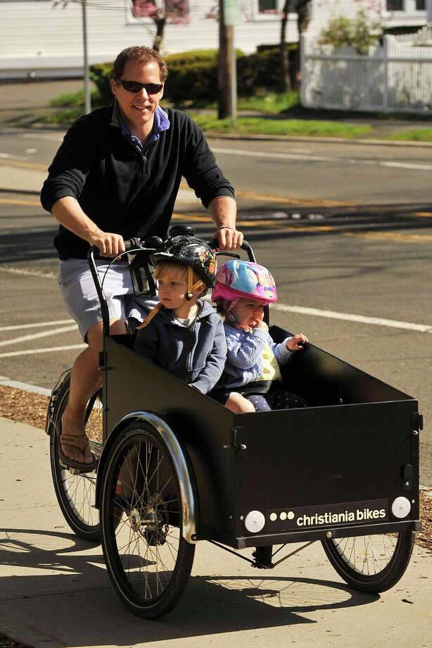 Bill Sterling pedals his children, Blake and Alexis, along Sound Beach Avenue during the 12th annual Old Greenwich - Riverside Community Center's Mother's Day Bike Ride at Old Greenwich Elementary School in Greenwich, Conn., on Sunday, May 11, 2014. Photo: Jason Rearick / Stamford Advocate
