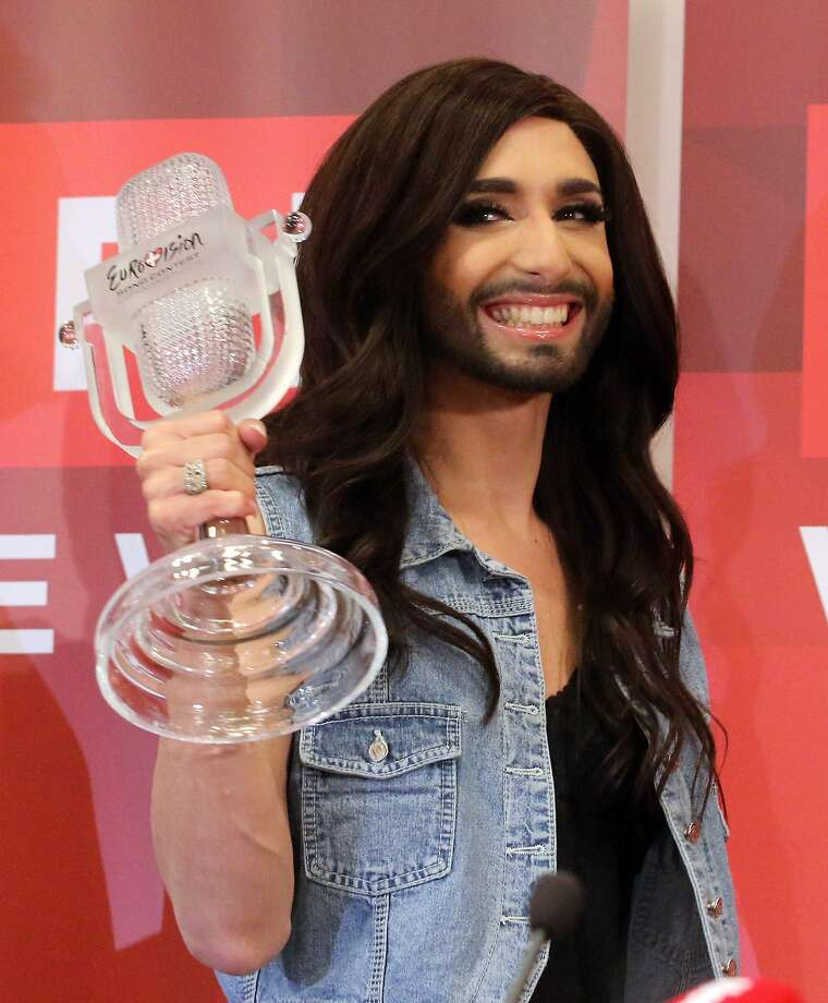 Austrian singer Conchita Wurst  arrives with the trophy at the  airport in Vienna Sunday May 11, 2014.  Bearded drag queen Conchita Wurst has made a triumphant return to Austria after winning the Eurovision Song Contest in Copenhagen Saturday,  in what the country's president called a victory for tolerance in Europe.  (AP Photo/Ronald Zak) Photo: Ronald Zak, Associated Press