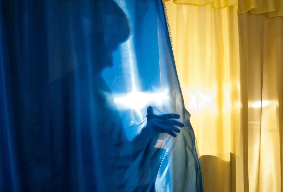A local resident casts a shadow on leaving a booth to cast her ballot at a polling station in Luhansk, Ukraine, on Sunday May 11, 2014. Residents of two restive regions in eastern Ukraine cast ballots Sunday in referendums, which seek approval for declaring sovereign people's republics in the Donetsk and Luhansk regions. (AP Photo/Evgeniy Maloletka) Photo: Evgeniy Maloletka, Associated Press