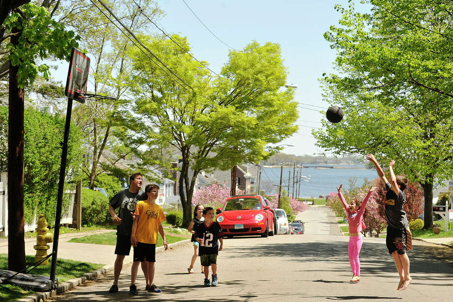 Gavin Dolan, right, shoots as, from left, Tom Dolan, Everett Dolan, Carolyn O'Halloran, Rory O'Halloran and Ella O'Halloran wait for the rebound during a pick-up game of basketball outside their home in Stamford, Conn., on Sunday, May 11, 2014. Photo: Jason Rearick / Stamford Advocate