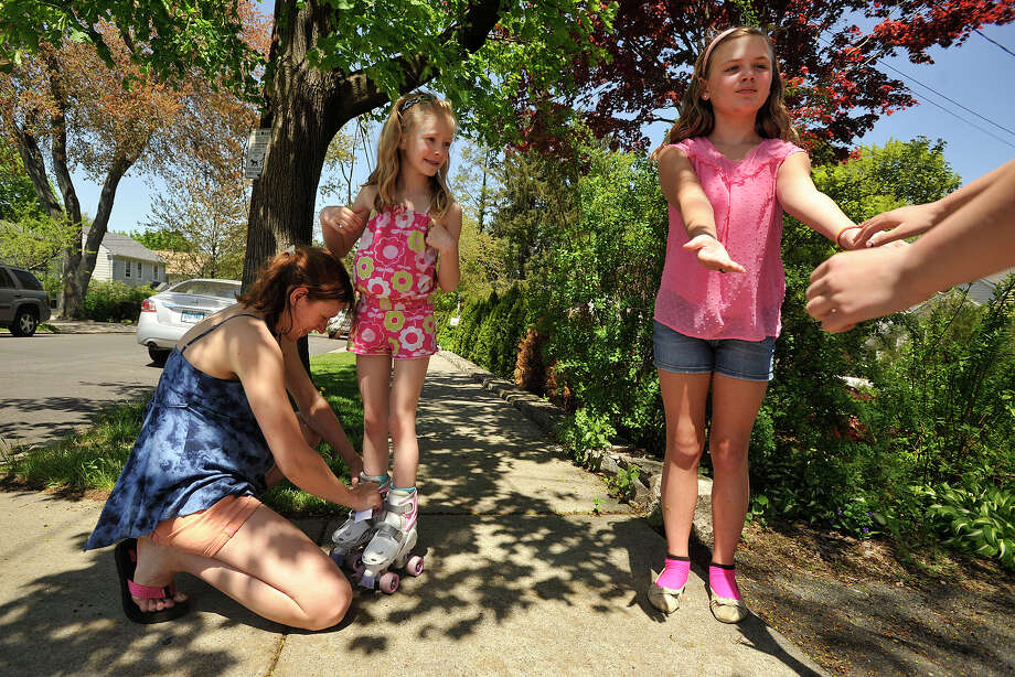 Hannah Ringel looks on as her mom, Wenke Ringel, adjusts her skates as her friend Bridget Sypniewski attempts to steady another friend outside their homes in Stamford, Conn., on Sunday, May 11, 2014. Photo: Jason Rearick / Stamford Advocate