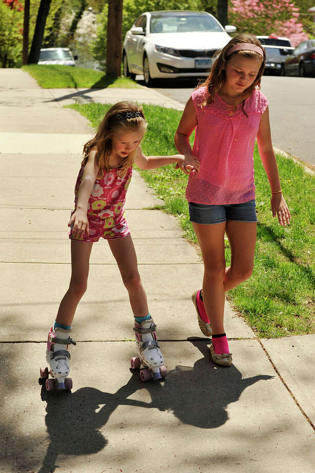 Bridget Sypniewski, right, steadies Hannah Ringel as she skates down a hill on the sidewalk outside their home in Stamford, Conn., on Sunday, May 11, 2014. Photo: Jason Rearick / Stamford Advocate