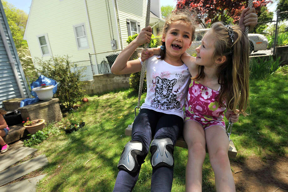 Kaete Weinseiss, left, and her friend Hannah Ringel swing together outside Ringel's home in Stamford, Conn., on Sunday, May 11, 2014. Photo: Jason Rearick / Stamford Advocate