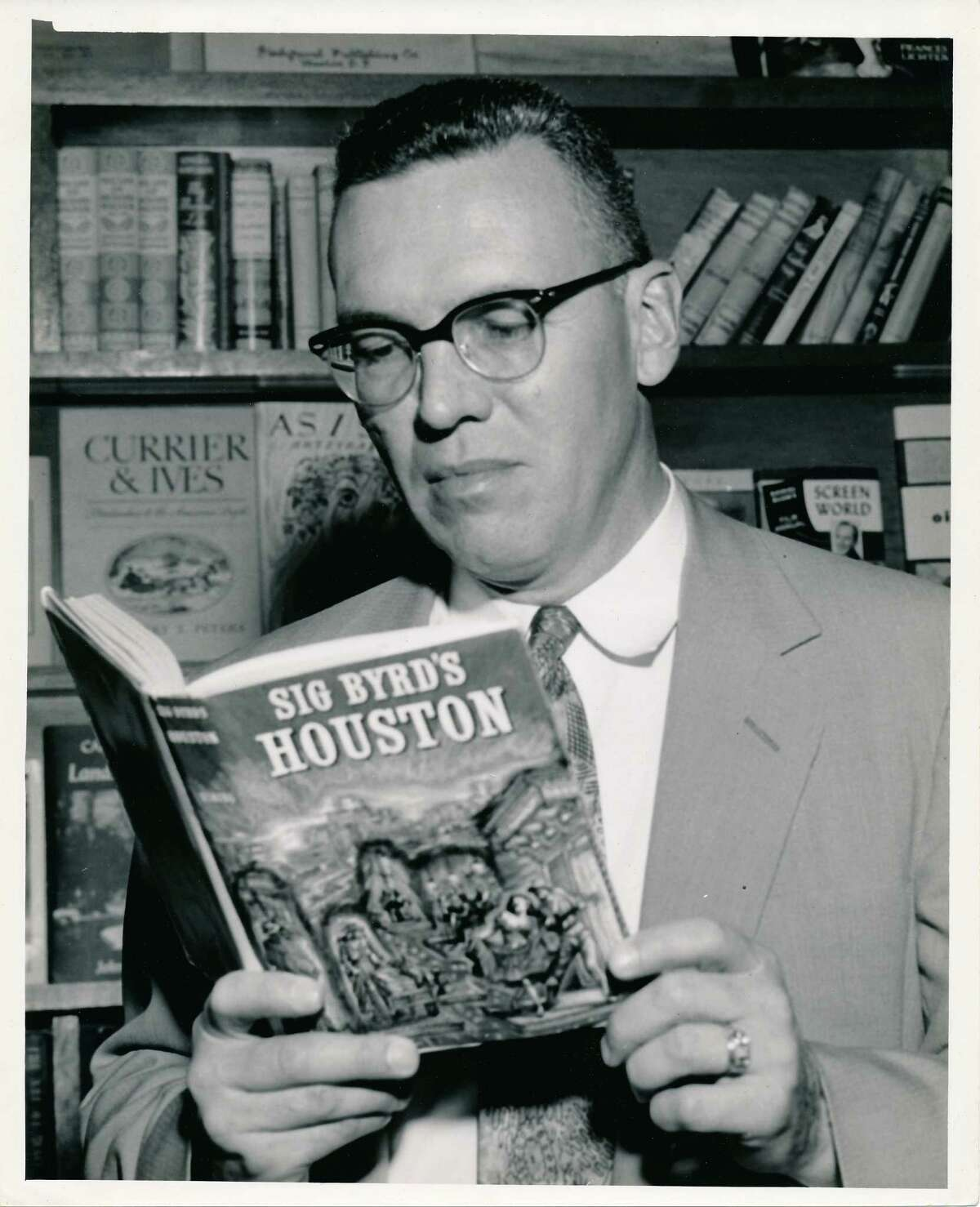 """Sigman Byrd, writer-columnist for Houston Chronicle, Post and Press. Here, Byrd looks over a copy of his book """"Sig Byrd's Houston"""" in the mid-1950s."""