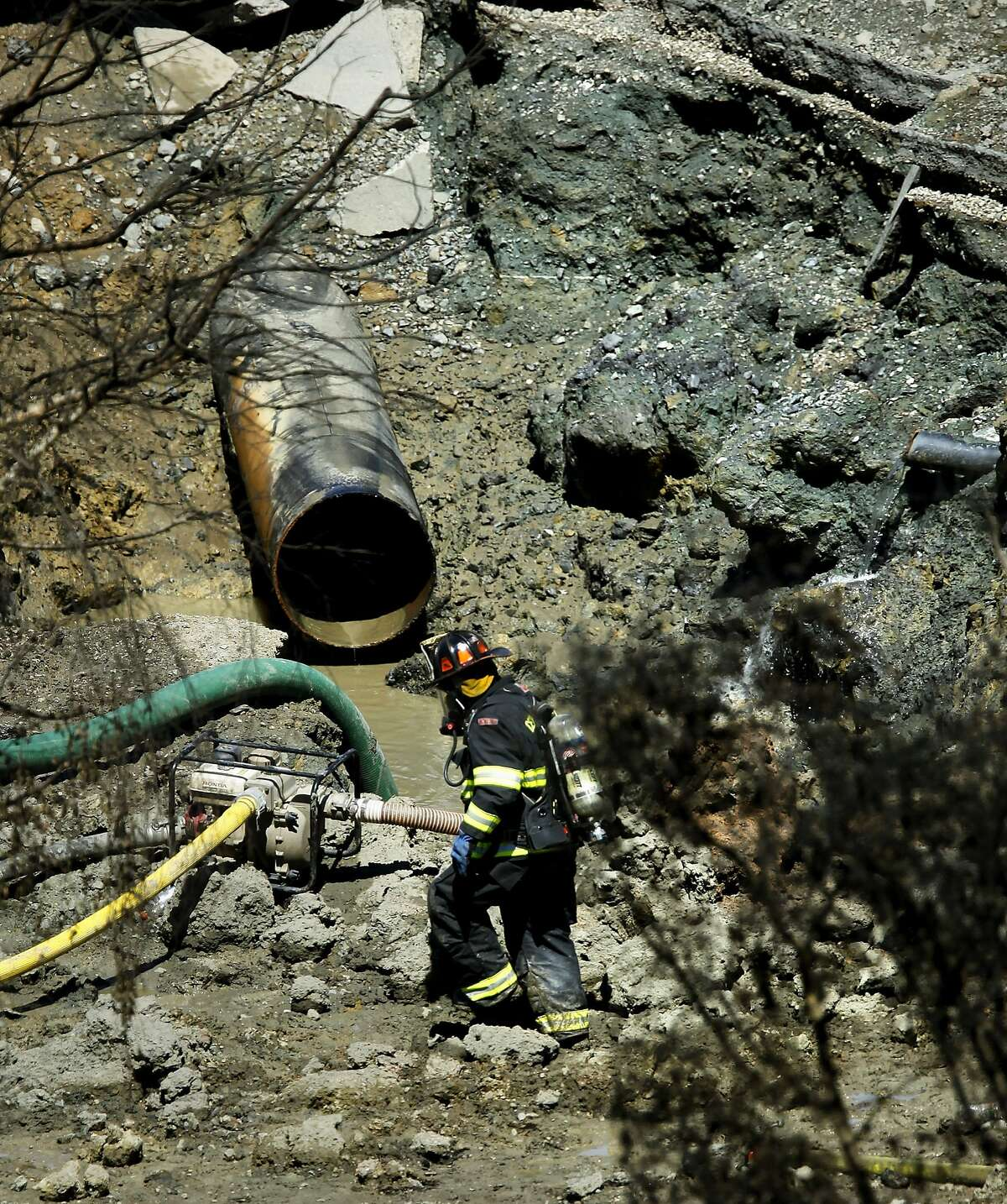 A firefighter at the blast site where the huge natural gas line in now exposed inside a large crater on Friday Sept. 10, 2010, in which an explosion and fire leveled the surrounding neighborhood the night before in San Bruno, Calif.