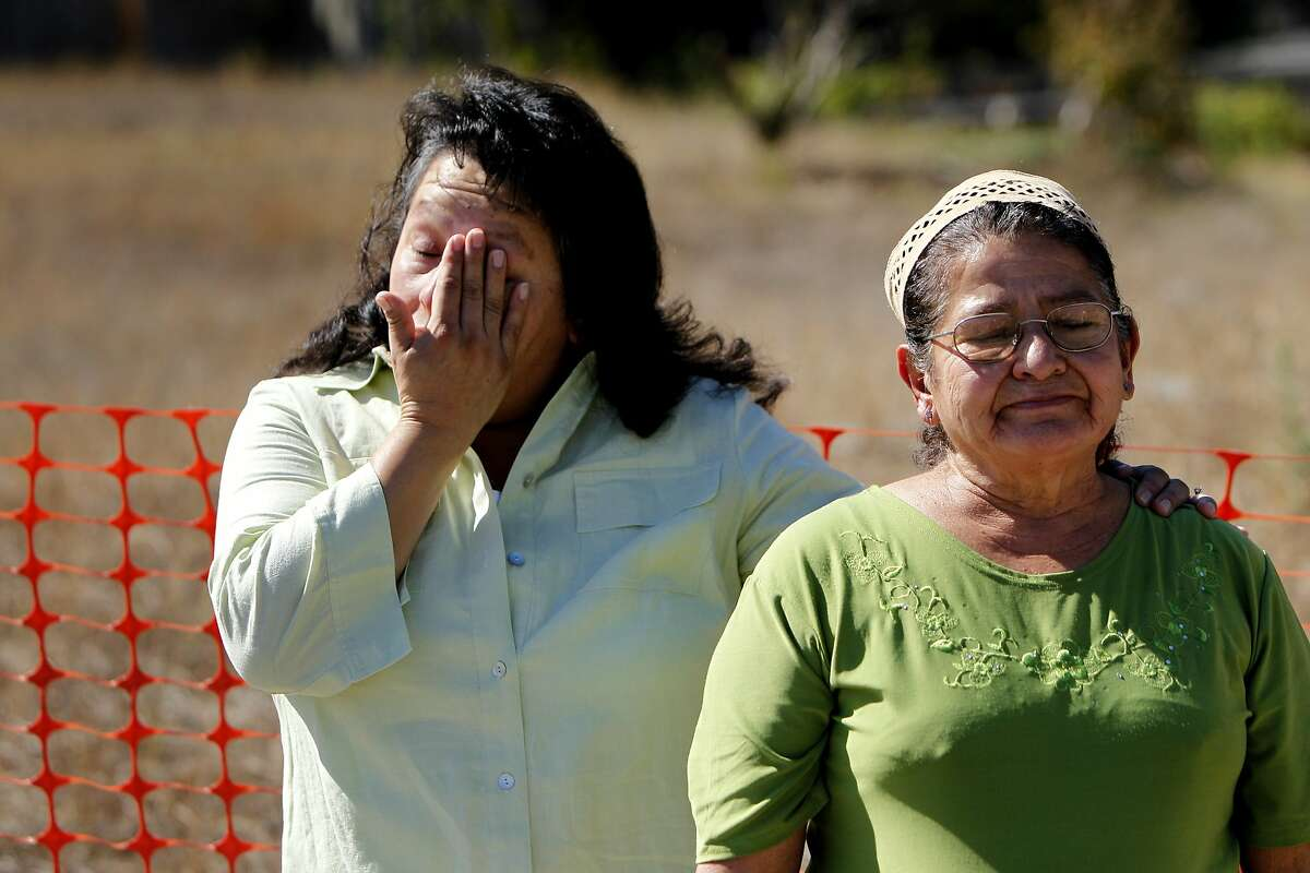 Christina, left and Irma Vides, residents of the San Bruno Crestmoor neighborhood are overcome by emotion after shoveling dirt into the crater, Tuesday September 20, 2011, at the corner of Glenview Drive and Earl in San Bruno, Calif. The city held a ceremony which allowed residents a chance to heal by shoveling dirt and starting to filling the crater which was created by the PG&E pipeline explosion last September 2010.