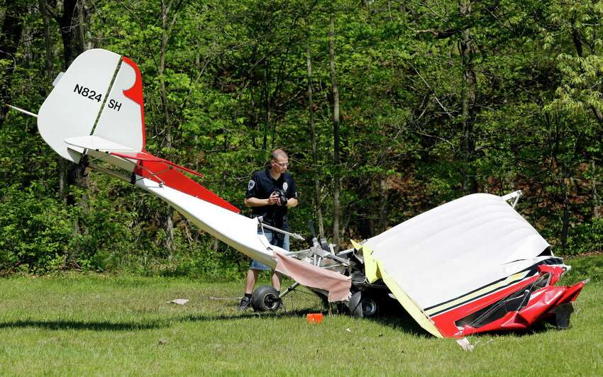 Jarid Larson of the Attica Police Department photographs the scene after a plane crash Saturday, May 10, 2014, off East Covered Bridge Road about three miles south of Attica, Ind. Sgt. Kim Riley says the crash killed the 72-year-old Charles H. Coffing of Covington who was flying the aircraft.