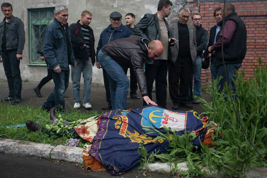 The body of a police officer killed during fighting between government forces and insurgents is covered with the flag of Mariupol as it lies outside a police station in Mariupol, eastern Ukraine, Friday, May 9, 2014. Fighting exploded Friday in Mariupol, a city of 500,000 on the Sea of Azov that is on the main road between Russia proper and Crimea. The fighting between government forces and insurgents in Mariupol has left several people dead. Photo: Alexander Zemlianichenko, AP  / AP2014