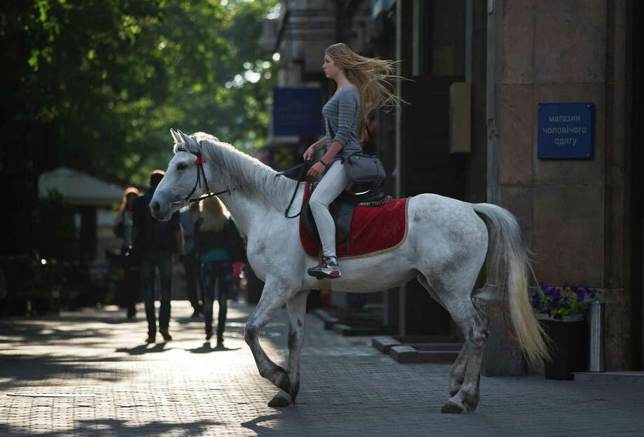 A girl rides a horse in Odessa, Ukraine, Sunday, May 11, 2014. Residents of two restive regions in eastern Ukraine engulfed by a pro-Russian insurgency voted Sunday in independence referendums seeking approval for declaring so-called sovereign people's republics in the Donetsk and Luhansk regions, while hundreds of pro-Russian protesters gathered in Odessa demanding similar action for their town. Photo: Vadim Ghirda, AP  / AP