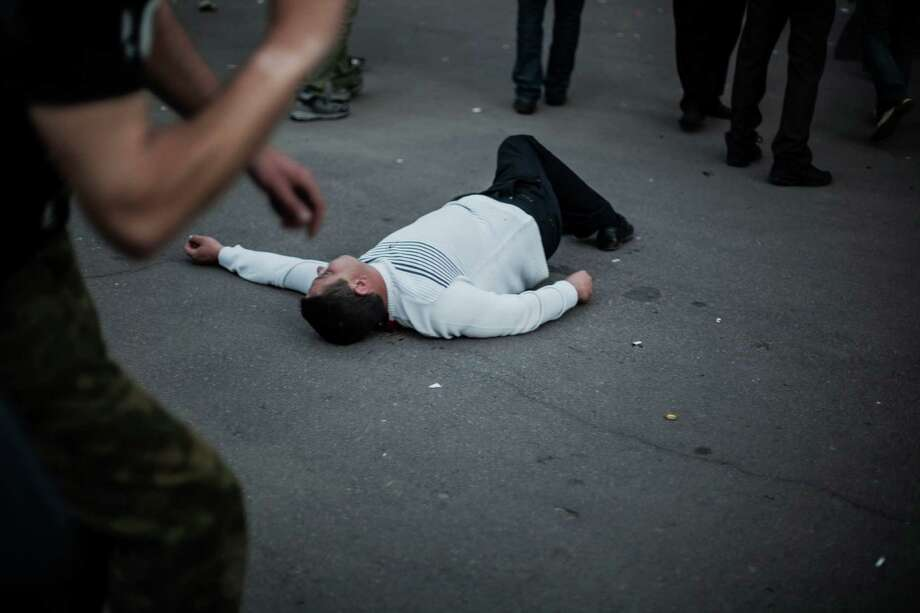 The body of a pro-Russia man lies on the ground in Krasnoarmeisk, Ukraine, Sunday, May 11, 2014. Although the voting in the Donetsk and Luhansk regions appeared mostly peaceful, Ukrainian national guardsmen opened fire on a crowd outside a town hall in Krasnoarmeisk, and an official with the region's insurgents said there were fatalities. Photo: Manu Brabo, AP  / AP