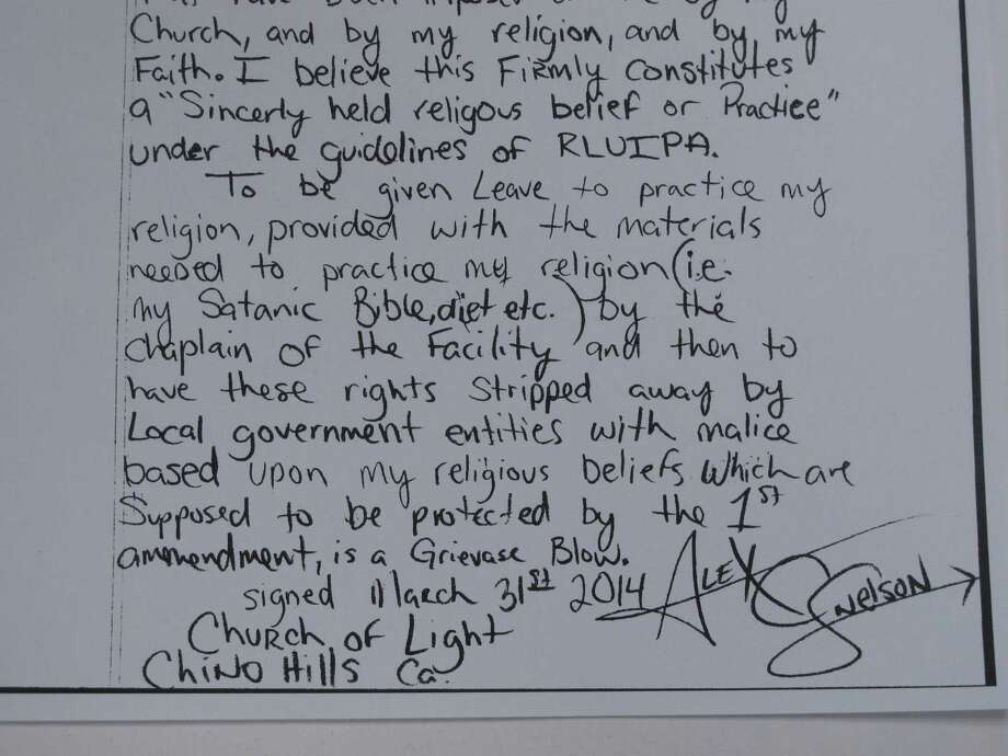 This May 9, 2014, photo,shows the closing of a hand-written lawsuit filed by Alex C. Snelson, a Nevada inmate who practices Satanism and accuses the Washoe County jail of violating his right to freely exercise his religion. Snelson, 33, said in the amended complaint filed in U.S. District Court in Reno on Wednesday that he's been denied meals that adhere to his religious diet. (AP Photo/Scott Sonner). Photo: Scott Sonner), AP  / AP