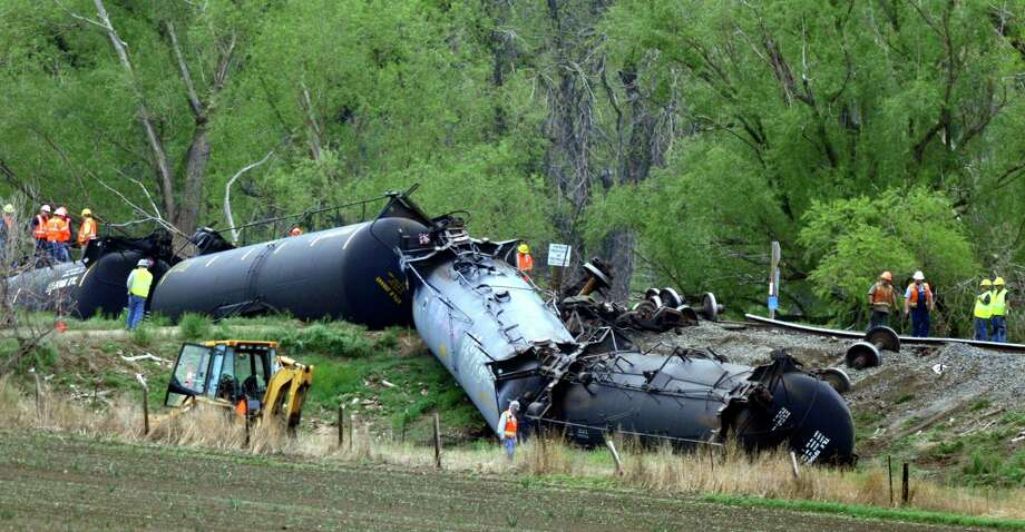 Crews work to clean up several train cars that were derailed and flipped along the track southwest of LaSalle, Colo. on Friday, May 9, 2014. The train, loaded in Windsor with Niobrara crude bound for New York, derailed around 8 a.m. according to Union Pacific Spokesman Mark Davis. Officials found one car of the 100-car train was leaking. Photo: Joshua Polson, AP  / The Greeley Tribune