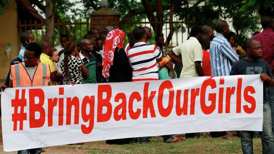"People attend a rally calling on the Government to rescue the school girls kidnapped from the Chibok Government secondary school, in Abuja, Nigeria, Saturday May 10, 2014. The president of Nigeria for weeks refused international help to search for more than 300 girls abducted from a school by Islamic extremists, one in a series of missteps that have led to growing international outrage against the government. The waiting has left parents in agony, especially since they fear some of their daughters have been forced into marriage with their abductors for a nominal bride price of $12. Boko Haram leader Abubakar Shekau called the girls slaves in a video this week and vowed to sell them. ""For a good 11 days, our daughters were sitting in one place,"" said Enoch Mark, the anguished father of two girls abducted from the Chibok Government Girls Secondary School. ""They camped them near Chibok, not more than 30 kilometers, and no help in hand. For a good 11 days."" Photo: Sunday Alamba, AP  / AP2014"
