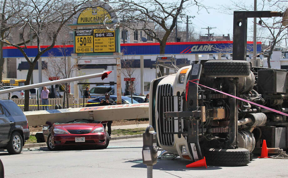 A crane lies on its side on Milwaukee's east side on Friday, May 9, 2014. Police say two people inside a car damaged in the fall were injured but did not seek medical attention. Three other damaged vehicles were unoccupied. Photo: Michael Sears, AP  / Milwaukee Journal Sentinel