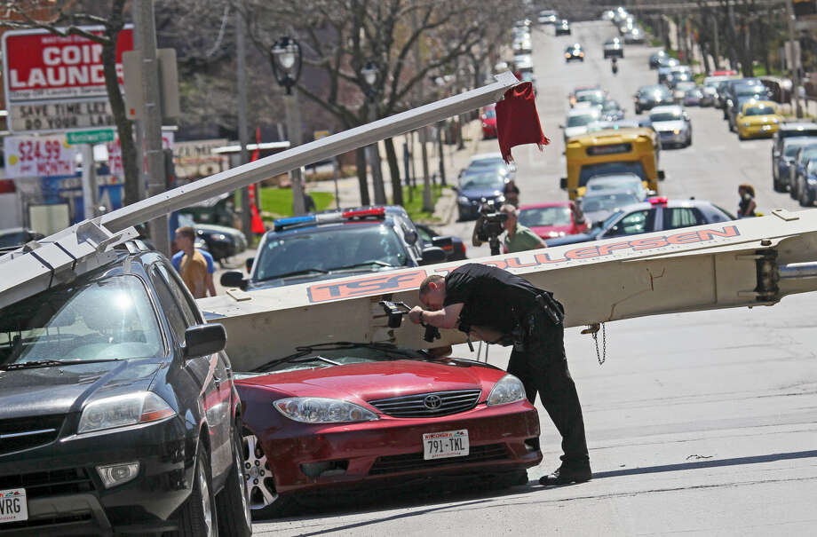 A police officer examines a damaged car after a crane toppled on Milwaukee's east side on Friday, May 9, 2014. Police say two people inside a car damaged in the fall were injured but did not seek medical attention. Three other damaged vehicles were unoccupied. Photo: Michael Sears, AP  / Milwaukee Journal Sentinel