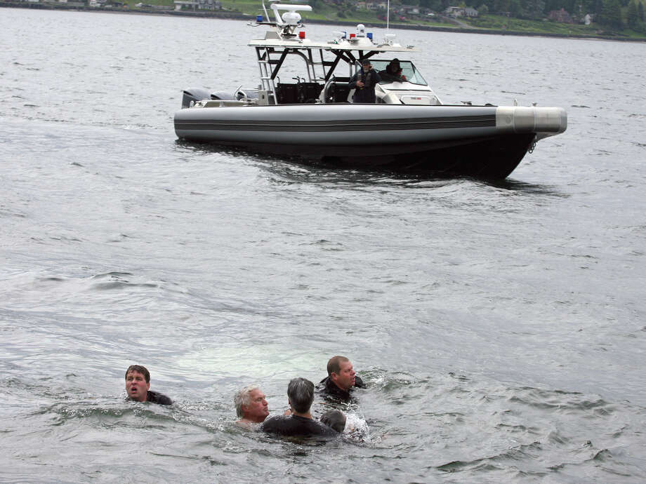 Bremerton Police Officer Bogen, top,  and volunteers pull the victim to shore from out of his submerged car off Bachmann Park Thursday, May 8, 2014, in Bremerton, Wa.  Police say an 88-year-old man suffering a medical emergency drove into the Sinclair Inlet Thursday at a Bremerton park. Photo: Larry Steagall, AP  / Kitsap Sun