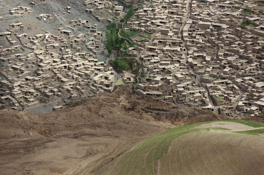 An aerial view shows the site of Friday's landslide that buried Abi Barik village in Badakhshan province, northeastern Afghanistan, Monday, May 5, 2014. Hundreds of people were killed in a horrific landslide and authorities are trying to help the 700 families displaced by the torrent of mud that swept through their village. The families left their homes due to the threat of more landslides, Minister for Rural Rehabilitation Wais Ahmad Barmak said. Photo: Rahmat Gul, AP  / AP2014