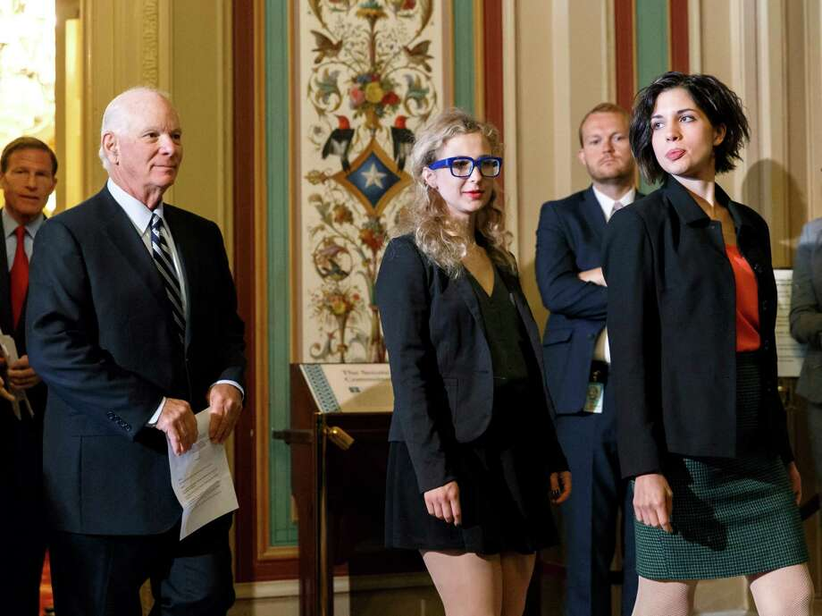 Russian political activists Nadya Tolokonnikova, right, and Maria Alyokhina, center, of the Russian punk band Pussy Riot, join Sen. Ben Cardin, D-Md., left, the chairman of the Helsinki Commission, and Sen. Richard Blumenthal, D-Conn., far left, in seeking action to stop violations of human rights by pro-Russian militants in the Ukraine region, at the Capitol in Washington, Tuesday, May 6, 2014. The political activists spent more than a year behind bars for performing songs critical of Russian leader Vladimir Putin. Photo: J. Scott Applewhite, AP  / AP2014