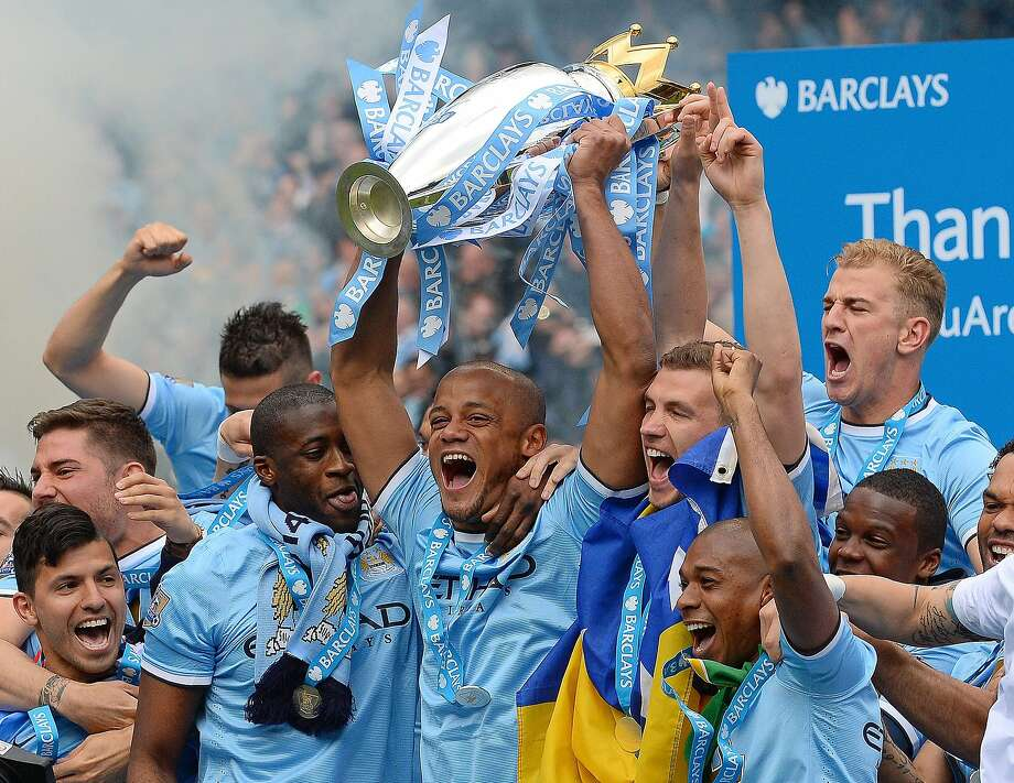 Manchester City's Vincent Kompany hoists the Premiership trophy to lead the celebration. Photo: Andrew Yates, AFP/Getty Images