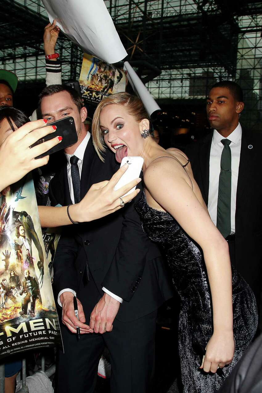 In this Saturday, May 10, 2014 photo released by Starpix, actors Jennifer Lawrence, center, and Nicholas Hoult, left, mug for a fans' mobile phone cameras during the premiere of