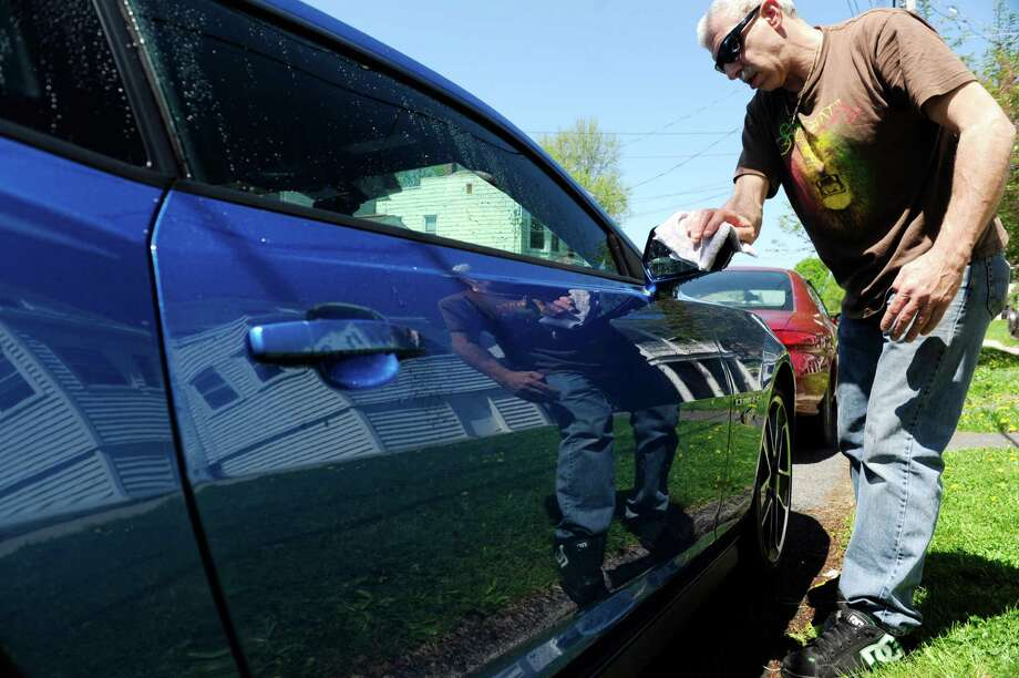 Tom Lossi washes his 2013 Chevy Camaro, Hot Wheels edition, outside his home on Sunday, May 11, 2014, in Rensselaer, N.Y.   (Paul Buckowski / Times Union) Photo: Paul Buckowski