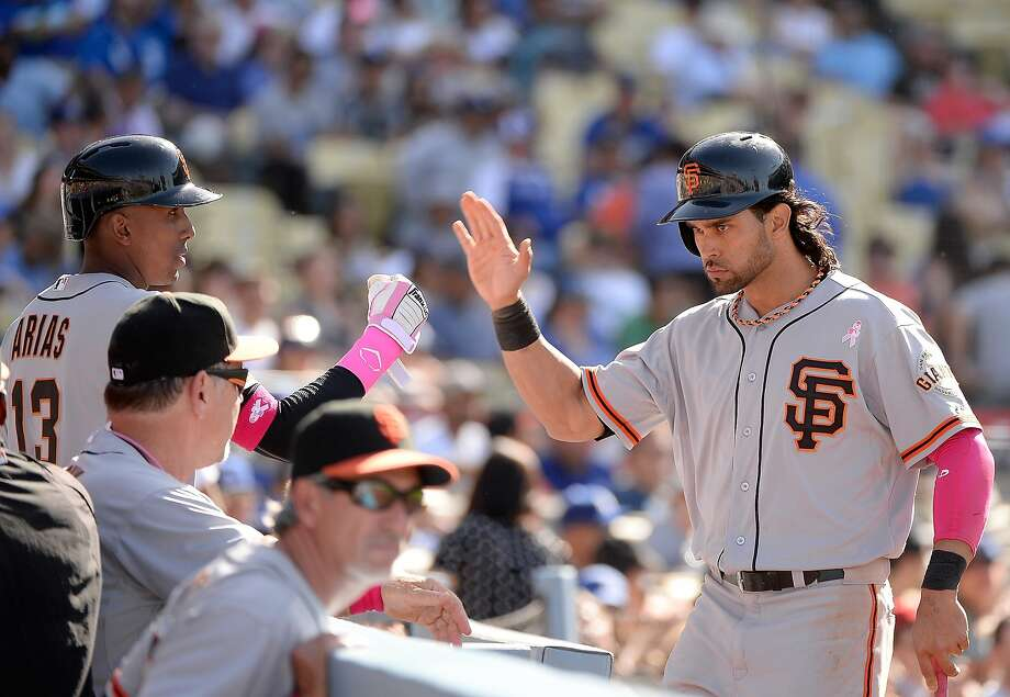 Angel Pagan (right), whose injury was a key to last year's slide, is greeted after scoring the go-ahead run in the 10th. Photo: Harry How, Getty Images