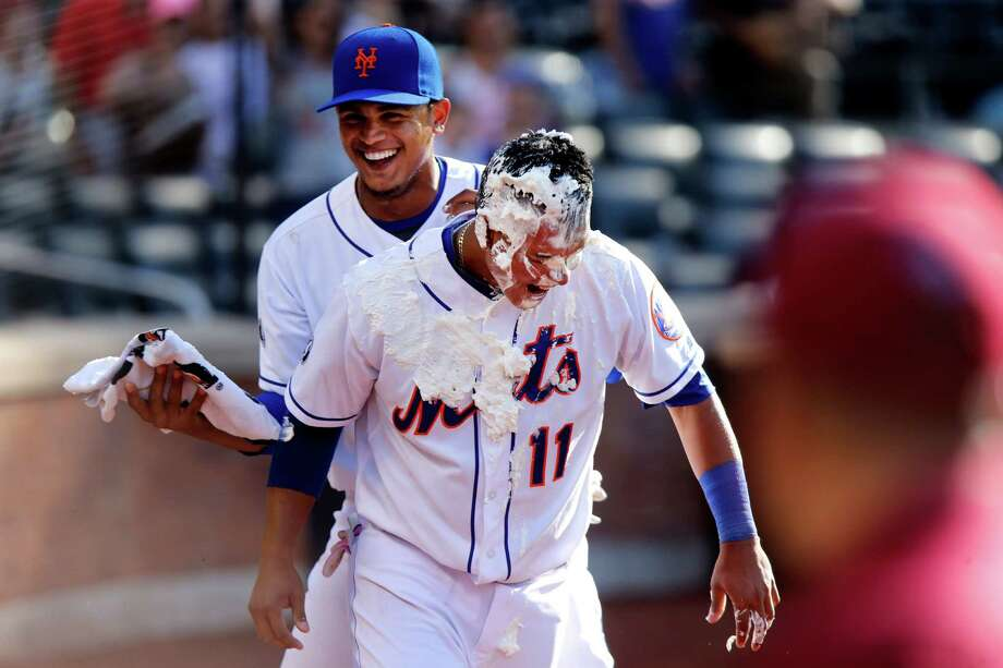New York Mets' Ruben Tejada, center, reacts to being hit by surprise with shaving cream by teammate Juan Lagares while giving a post-game interview after he hit a game-winning RBI single during the 11th inning of a baseball game against the Philadelphia Phillies, Sunday, May 11, 2014, in New York.  New York won 5-4 in 11 innings. (AP Photo/Jason DeCrow) ORG XMIT: NYJD115 Photo: Jason DeCrow / FR103966 AP