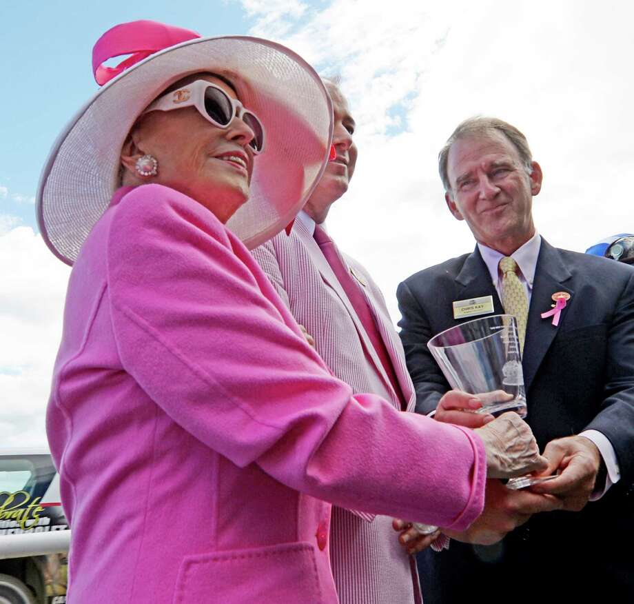 Marylou Whitney, left, and John Hendrickson, center, are awarded a Tiffany vase from NYRA president Chris Kay, right, Wednesday, Aug 14, 2013, at Saratoga Race Course in Saratoga Springs, N.Y.  Whitney was given the 2013 Fabulous Fillies Day award for her notable philanthropy, including her work with the back stretch workers. All fans who wore pink in support of the Breast Cancer Research Foundation received free admission to the clubhouse and grandstand during NYRA's salute to women. (Skip Dickstein/Times Union) Photo: SKIP DICKSTEIN