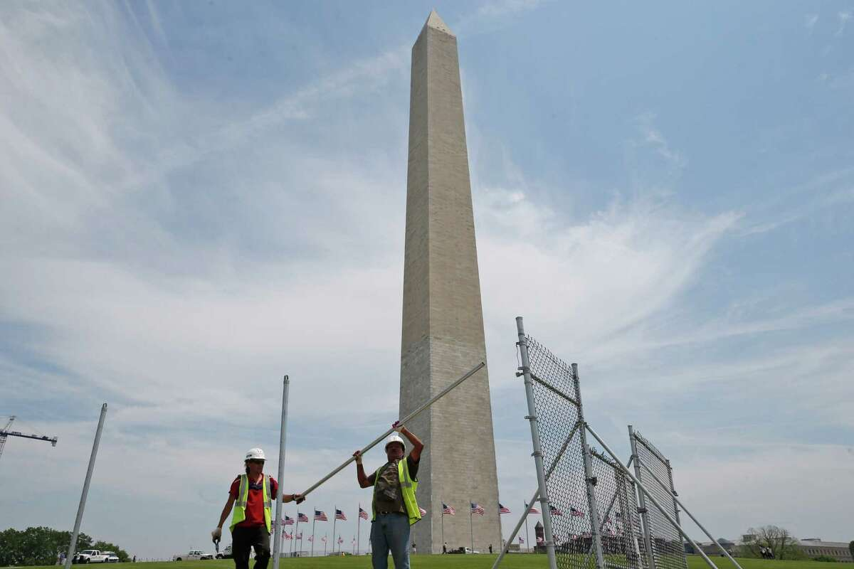 In this Friday, May 9, 2014 photo, workers Julio Dichis, right, and Jose Oreyana remove the fencing which closed the Washington Monument off to the public during renovations Washington. The monument, which sustained damage from an earthquake in August 2011, will re-open to the public on Monday, May 12, 2014. (AP Photo/Charles Dharapak/)