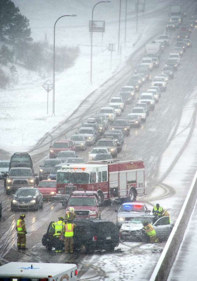 Firefighters work the scene of a two car injury accident that was one of many that slowed traffic on I-25 at the Monument exit north of Colorado Springs, Colo. as a spring snowstorm swept through Colorado Sunday, May 11, 2014. (AP Photo/The Gazette, Mark Reis) Photo: MARK REIS, MBI / THE GAZETTE