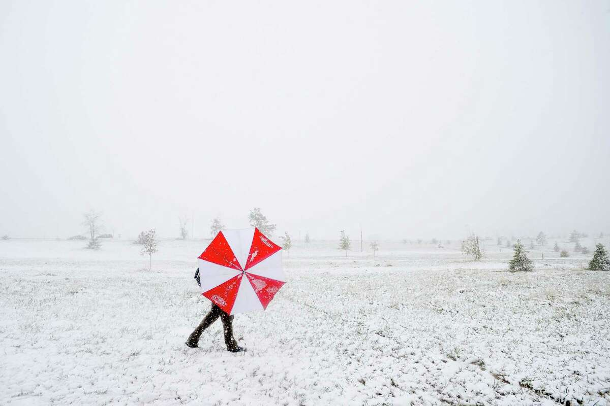 Pat Blazek shields himself from the snow and wind with an umbrella as he competes in a disc golf tournament Sunday, May 11, 2014, at Aggie Greens in Fort Collins, Colo. Snow is expected to fall through Monday, with highs reaching the sixties later this week. (AP Photo/The Coloradoan, Erin Hull)