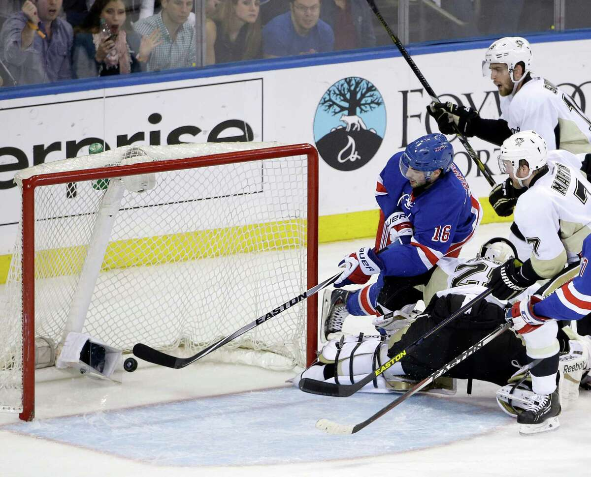 New York's Derick Brassard (16) slices past Pittsburgh goaltender Marc-Andre Fleury to score in the Rangers' 3-1 victory over the visiting Penguins.