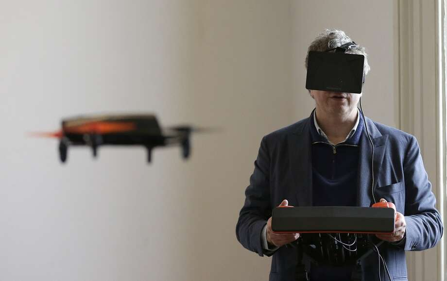 In this Thursday, May 8, 2014 photo, Parrot CEO Henri Seydoux flies a Parrot Bebop drone using the Skycontroller while wearing an Oculus headset during a demonstration at a Parrot event in San Francisco. The Parrot Bebop drone, which has a 14-megapixel fish-eye camera lens and battery life of about 12 minutes flying time, is scheduled to be released later this year. (AP Photo/Jeff Chiu) Photo: Jeff Chiu, Associated Press
